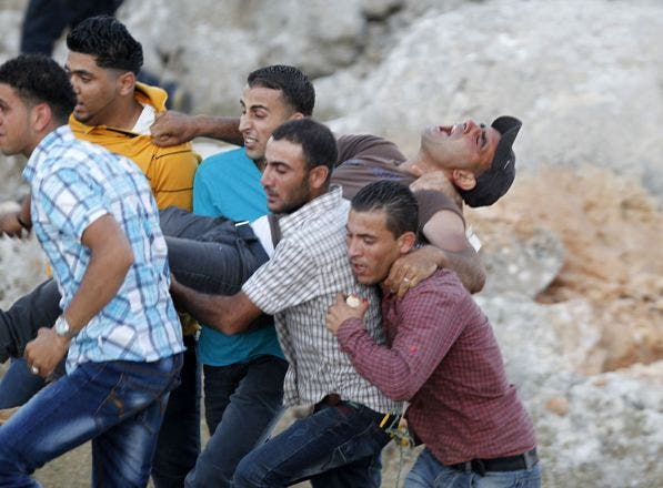 Palestinians carry an injured man who was shot by Israeli security forces during clashes in the West Bank village of Silwad on August 8, 2014 following a demonstration against the Israeli army's Gaza campaign. Israeli warplanes pounded targets across Gaza, where at least five Palestinians were killed and militants fired dozens of rockets into Israel after renewed hostilities ruptured a fledgling three-day truce. AFPAFP PHOTO / ABBAS MOMANI