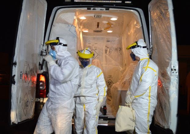 An ambulance is readied by technicians wearing biological hazard protective clothes to transport a Guinean patient suspected of having contracted Ebola, in Cascavel, state of Parana, Brazil, on October 10, 2014. Brazilian health officials have quarantined a Guinean man feared to have Ebola after he checked in at a clinic with a fever following his arrival from Africa last month. The 47-year-old man was taken in an air force plane from the southern state of Parana to the National Infectious Disease Institute in Rio de Janeiro on Friday morning after arriving at a health center in the town of Cascavel with a fever the previous afternoon. The patient arrived in Brazil on September 19.  AFP PHOTO/LUIZ CARLOS CRUZ