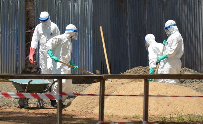 Health workers from the Liberian Red Cross wear protective gear as they shovel sand which will be used to absorb fluids emitted from the bodies of Ebola victims in front of the ELWA 2 Ebola management center in Monrovia on October 23, 2014. African nations will send more than 1,000 health workers to Ebola-ravaged Liberia, Sierra Leone and Guinea, the head of the African Union Commission said on October 23, 2014. AFP PHOTO / ZOOM DOSSO