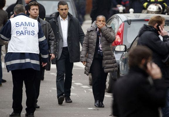 French Justice Minister Christiane Taubira reacts outside of the headquarters of the French satirical newspaper Charlie Hebdo in Paris on January 7, 2015, after armed gunmen stormed the offices leaving twekve dead. At least 12 people were killed when gunmen armed with Kalashnikovs and a rocket-launcher opened fire in the offices of French satirical weekly Charlie Hebdo on January 7. AFP PHOTO / KENZO TRIBOUILLARD