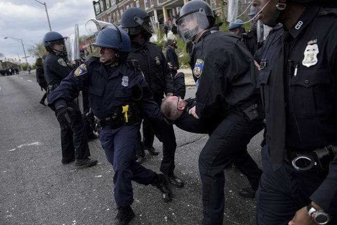 TOPSHOTSBaltimore police officers carry an injured comrade from the streets near Mondawmin Mall April 27, 2015 in Baltimore, Maryland. Violent street clashes erupted in Baltimore on Monday after friends and family gathered for the funeral of Freddie Gray, a 25-year-old black man whose death in custody triggered a fresh wave of protests over US police tactics. Police said at least seven officers were injured -- one of them was unresponsive -- as youths hurled bricks and bottles and destroyed at least one police vehicle in the vicinity of the shopping mall not far from the church where the funeral took place.  AFP PHOTO/BRENDAN SMIALOWSKI
