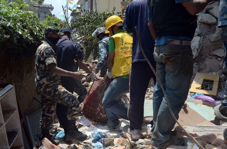 Rescatistas trasladas cadáveres de las víctimas del terremoto.
