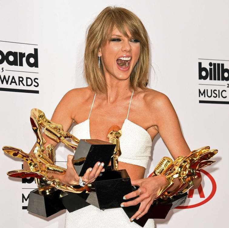 """(FILES) This May 17, 2015 file photo shows Taylor Swift as she poses in the press room iwth her awards at the 2015 Billboard Music Awards, at the MGM Grand Garden Arena in Las Vegas, Nevada. Pop superstar Taylor Swift said June 25, 2015 she would stream her latest album exclusively on Apple, capping an 180-degree shift after she threatened a boycott. Swift on Sunday issued an open protest to Apple over compensation to artists on its upcoming streaming service, leading the tech giant to reverse course and step up payments. In response, the 25-year-old singer, who had initially threatened a boycott, said Thursday that she would stream her blockbuster album """"1989"""" on Apple Music exclusively. AFP PHOTO / ROBYN BECK"""