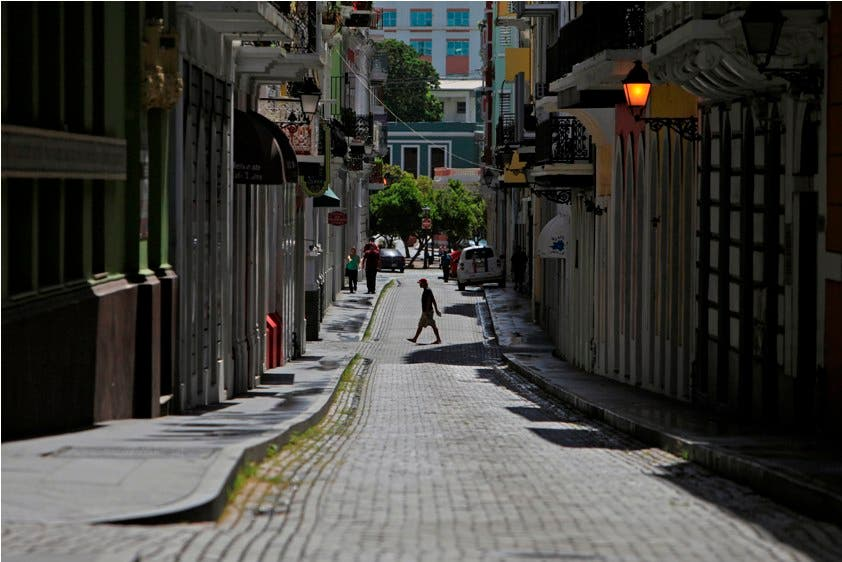 Un hombre cruza una calle de adoquines en el distrito colonial de Viejo San Juan, en Puerto Rico.