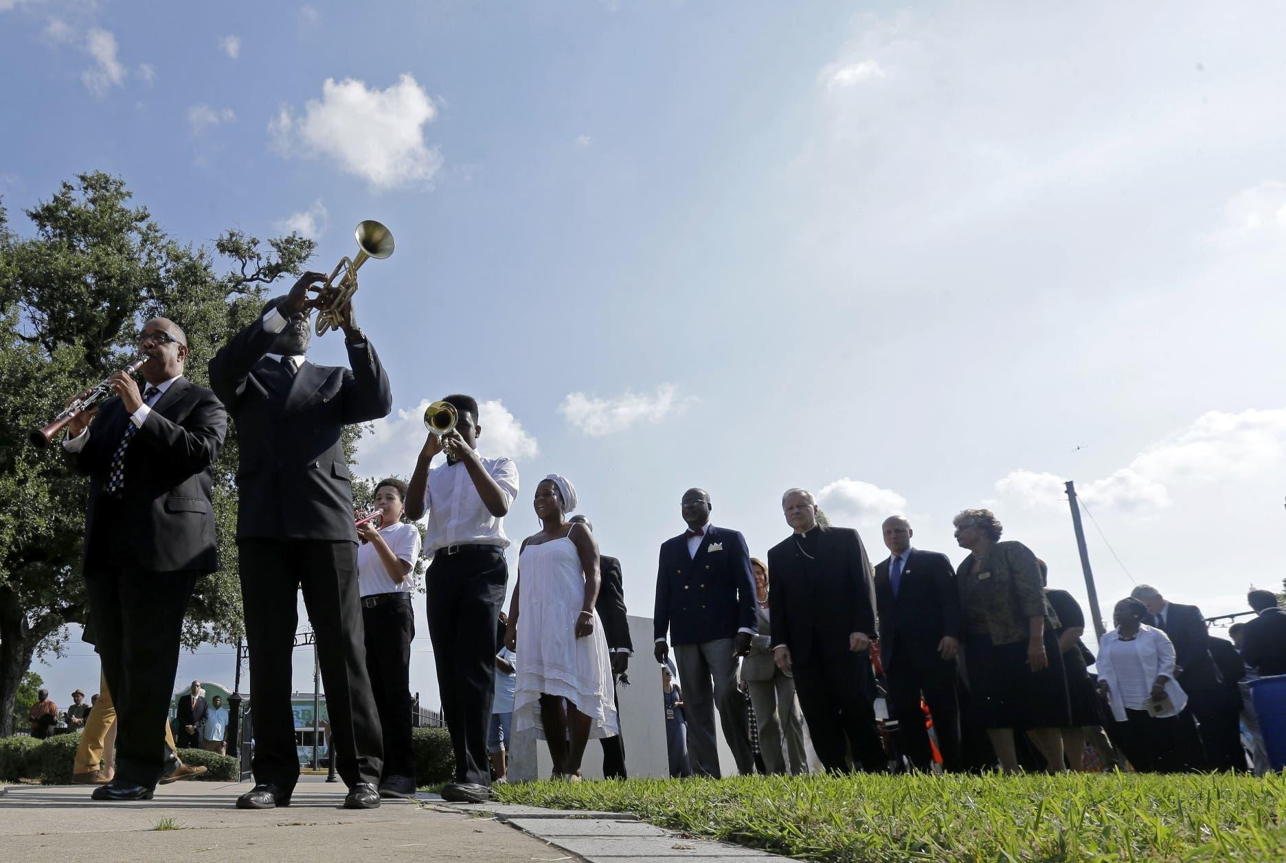 Músicos encabezan una procesión durante una ceremonia de colocación de una ofrenda floral en un monumento a las víctimas del huracán Katrina, en el 10mo aniversario de esa tempestad que azotó Nueva Orléans. (AP Foto/Gerald Herbert)