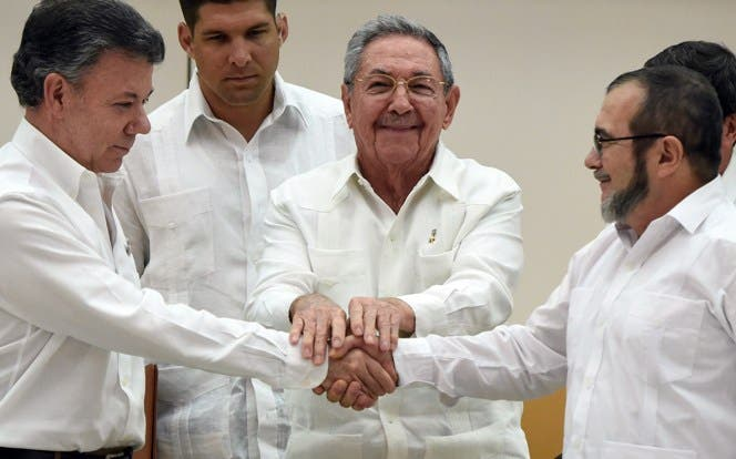 "TOPSHOTS Colombian President Juan Manuel Santos (L) and the head of the FARC guerrilla Timoleon Jimenez, aka Timochenko (R), shake hands as Cuban President Raul Castro (C) holds their hands during a meeting in Havana on September 23, 2015. The Colombian government and FARC rebels announced a key breakthrough in their nearly three-year peace talks Wednesday with the signing of a deal on justice for crimes committed during the five-decade conflict. The deal includes the creation of special courts and a broad amnesty, though this will not cover ""crimes against humanity, serious war crimes"" and other offenses including kidnappings, extrajudicial executions and sexual abuse, said officials from Cuba and Norway, the guarantors in the talks. AFP PHOTO / Luis Acosta"