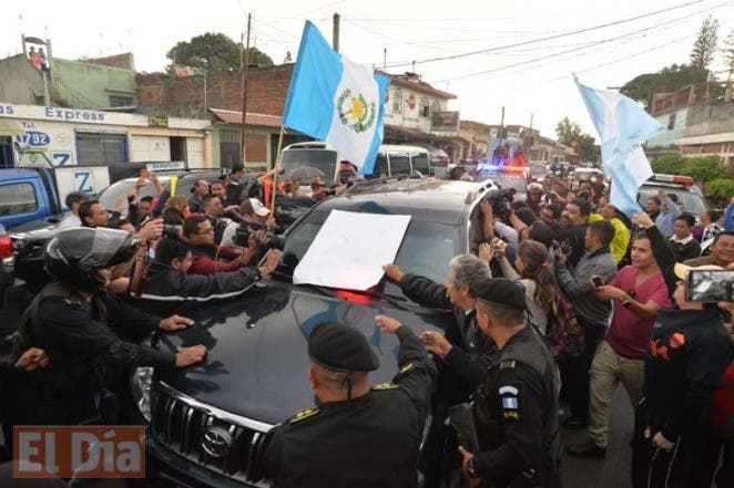 Demonstrators surround the vehicle carrying former Guatemalan President Otto Perez upon arrival at the Matamoros military barracks in Guatemala City on September 3, 2015. Judge Miguel Angel Galvez ordered the detention Thursday of Guatemala's disgraced president Otto Perez, hours after he resigned his post amid a massive corruption scandal.     AFP PHOTO / ORLANDO ESTRADA