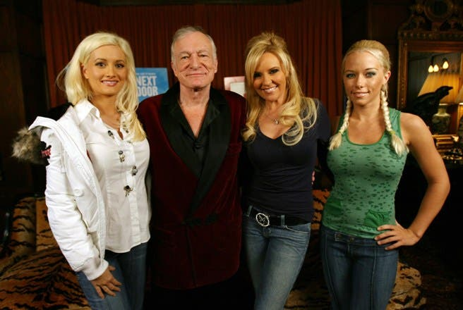 """(FILES) A file picture taken on January 11, 2007 at the Playboy Mansion in Beverly Hills, shows US Playboy Magazine publisher Hugh Hefner (2ndL) posing with his three girl friends:  Holly Madison (L), Bridget Marquardt (2R), and Kendra Wilkinson (R), during a press conference to introduce the new season of Hefner's TV show """"Girls of the Playboy Mansion"""" on E! Entertainment. Playboy will stop publishing the photographs of the fully nude women so closely associated with it, declaring such pictures have become """"passe"""" in the Internet age where free pornography is readily available. Starting in March, Playboy's revamped print edition will still include photographs of women in provocative poses.  AFP PHOTO / GABRIEL BOUYS"""