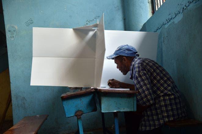 Un hombre arroja papeletas en una votación Su estación en la vida de Petion Ville durante las elecciones presidenciales en Puerto Príncipe el 25 de octubre de 2015. Haití es la celebración de elecciones presidenciales, elecciones legislativas y municipales.
