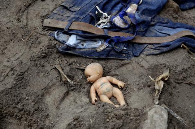 Una muñeca y alguna ropa quedan tendidas en el lugar, mientras los rescatistas continúan la búsqueda en el lugar donde se sucitó un alud en Cambray, un vecindario del suburbio de Santa Catarina Pinula, a las afueras de Ciudad de Guatemala, el sábado 3 de octubre de 2015. El sábado se recuperaron más cuerpos luego de que se colapsara una ladera sobre una zona residencial y se teme que haya más personas enterradas en los escombros. (Foto AP/Luis Soto)