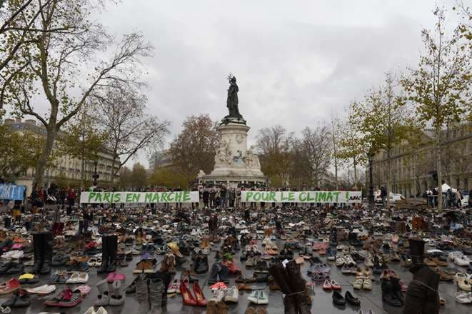 """TOPSHOTS The Place de la Republique is covered in pairs of shoes on November 29, 2015 in downtown Paris, as part of a symbolic and peaceful rally called by the NGO Avaaz """"Paris sets off for climate"""" within the UN conference on climate change COP21, as an attempt to get round the French authorities' ban on public gatherings. Paris has extended a ban on public gatherings introduced after the terror attacks in the French capital until November 30, the start of UN climate talks, where some 150 leaders will be tasked with reaching the first truly universal climate pact. AFP PHOTO / MIGUEL MEDINA"""