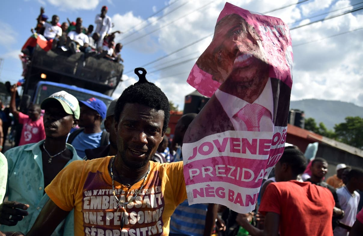 Supporters of ruling party candidate, Jovenel Moise, of PHTK political party, during a march in Port-au-Prince, Haiti on February 2, 2016. Haiti's electoral authority postponed the planned January 24 presidential run-off amid mounting opposition street protests and voting fraud allegations. Martelly's term ends February 7, and with no successor in place, Haiti is facing constitutional crisis. Haiti's electoral authority postponed the planned January 24 presidential run-off amid mounting opposition street protests and voting fraud allegations. Martelly's term ends February 7, and with no successor in place, Haiti is facing constitutional crisis.  / AFP / HECTOR RETAMAL
