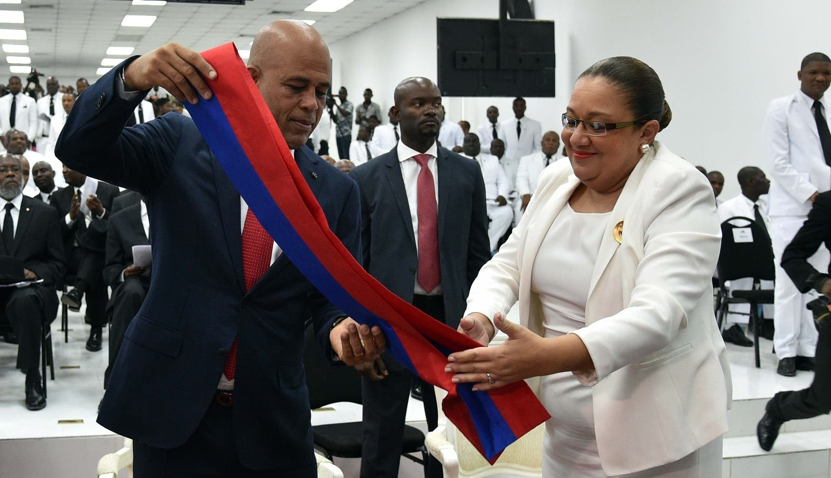Haitian President, Michel Martelly(C)with the help of First Lady Sophia Martelly, removes his presidential sash during the ceremony in the Haitian Parliament February 7, 2016 in Port-au-Prince where Martelly gave his last address to the nation before stepping down as president. Haitian politicians inked a last-minute agreement to install a transitional government February 6, just hours before President Michel Martelly was scheduled to step down with no replacement in line. / AFP / HECTOR RETAMAL