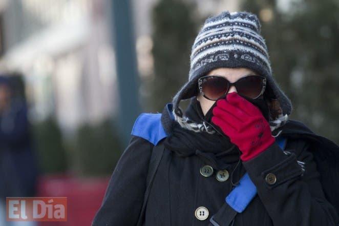 Una mujer se coloca la bufanda sobre la nariz y la boca para protegerse del frío en Nueva York. AP