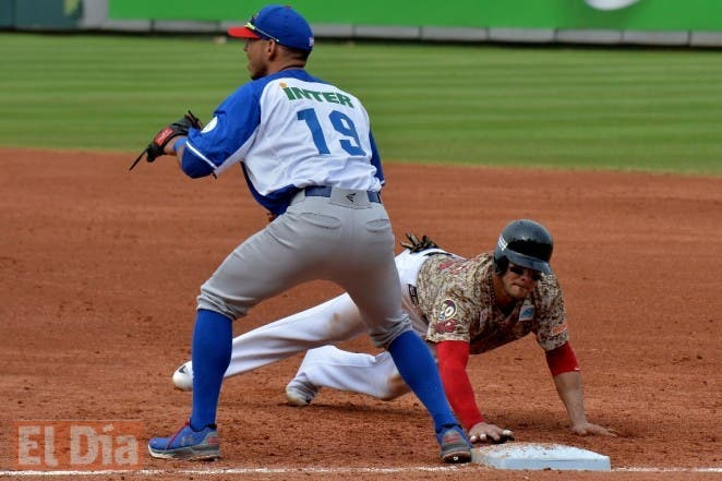 Infielder Neftali Soto of Puerto Rico makes an out on first base against Felix Perez of Venezuela during their 2016 Caribbean baseball series game on February 1, 2016 in Santo Domingo.   AFP PHOTO/YAMIL LAGE