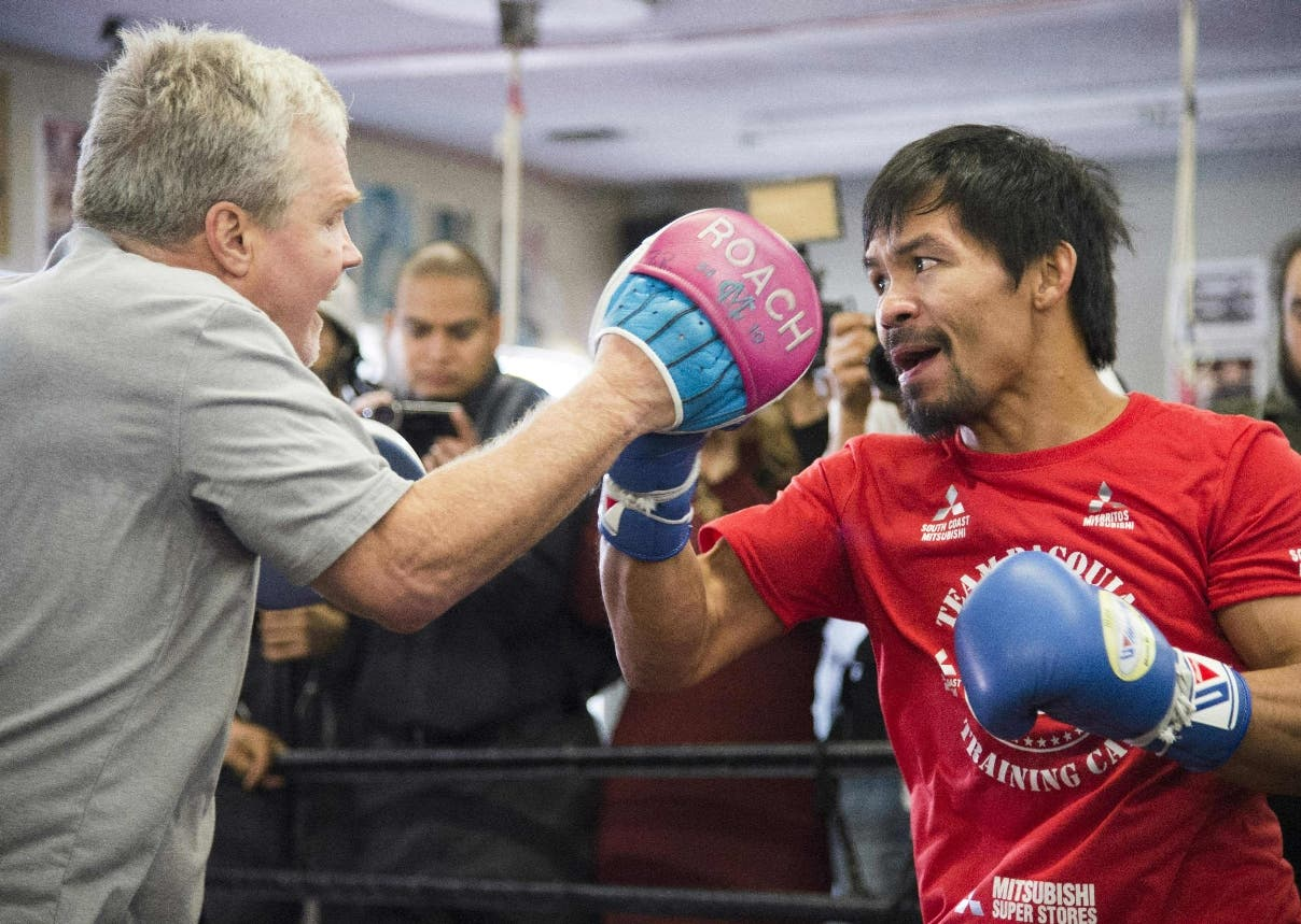 Trainer Freddie Roach works out with Filipino boxer Manny Pacquiao at the Wild Card Boxing Club in Hollywood, California, March 30, 2016.  Pacquiao is in final preparation for his 12-round welterweight championship fight against Timothy Bradley, Jr. on April 9, 2016 in Las Vegas, Nevada. Veteran trainer Freddie Roach has vowed to back Pacquiao if the boxer decides to take advantage of rule changes which could see professional fighters allowed to take part in this summer's Olympics. / AFP / ROBYN BECK