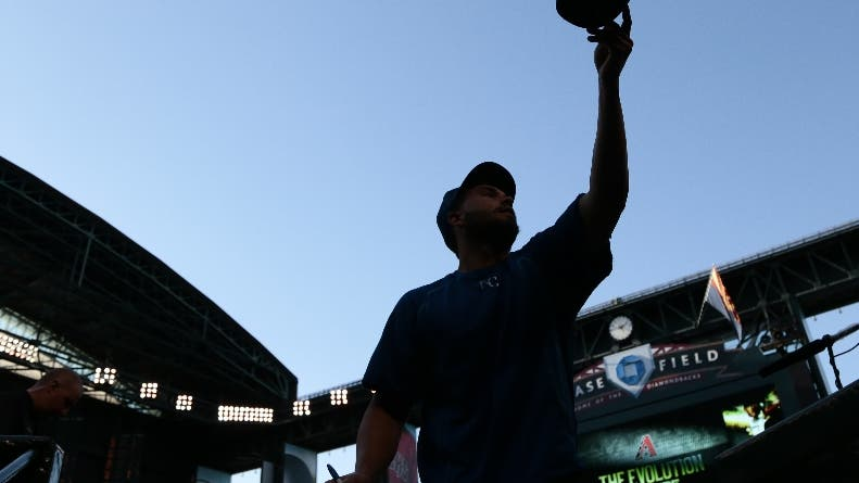 Kansas City Royals' Eric Hosmer tosses a hat back to a fan after signing it before the team's spring training baseball game against the Arizona Diamondbacks Friday, April 1, 2016, in Phoenix. (AP Photo/Jae C. Hong)