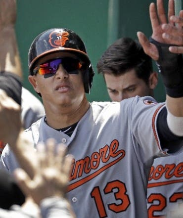 Baltimore Orioles' Manny Machado celebrates in the dugout after scoring on a single by Mark Trumbo during the first inning of a baseball game against the Kansas City Royals, Sunday, April 24, 2016, in Kansas City, Mo. (AP Photo/Charlie Riedel)