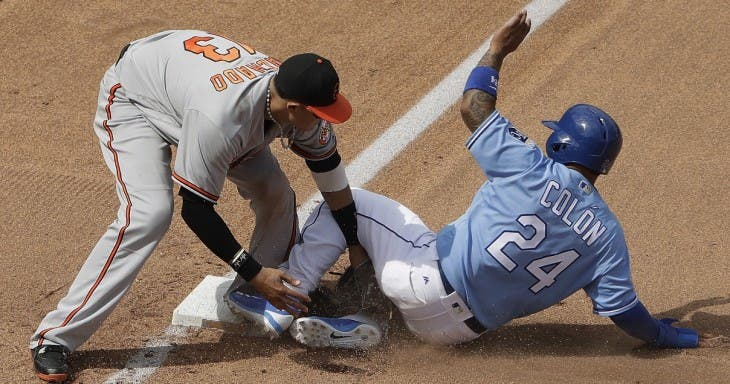 Kansas City Royals' Christian Colon (24) is tagged out at third by Baltimore Orioles third baseman Manny Machado (13) as he tried to reach on a fielder's choice hit into by Jarrod Dyson during the seventh inning of a baseball game Sunday, April 24, 2016, in Kansas City, Mo. (AP Photo/Charlie Riedel)