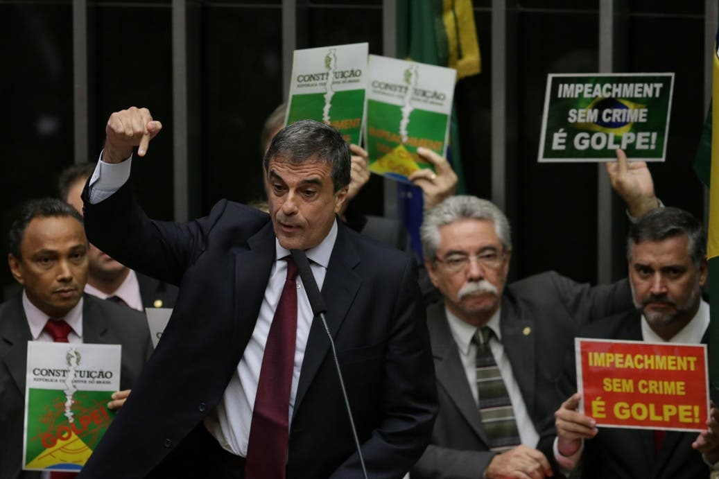 "Brazil's Attorney General Jose Eduardo Cardozo, backed by posters behind that say in Portuguese ""Impeachment without a crime is a coup,"" defends Brazil's President Dilma Rousseff during a debate on impeaching her in the Chamber of Deputies in Brasilia, Brazil, Friday, April 15, 2016. The lower chamber of Brazil's Congress began the debate on whether to impeach Rousseff, a question that underscores deep polarization in Latin America's largest country and most powerful economy. (AP Photo/Eraldo Peres)"