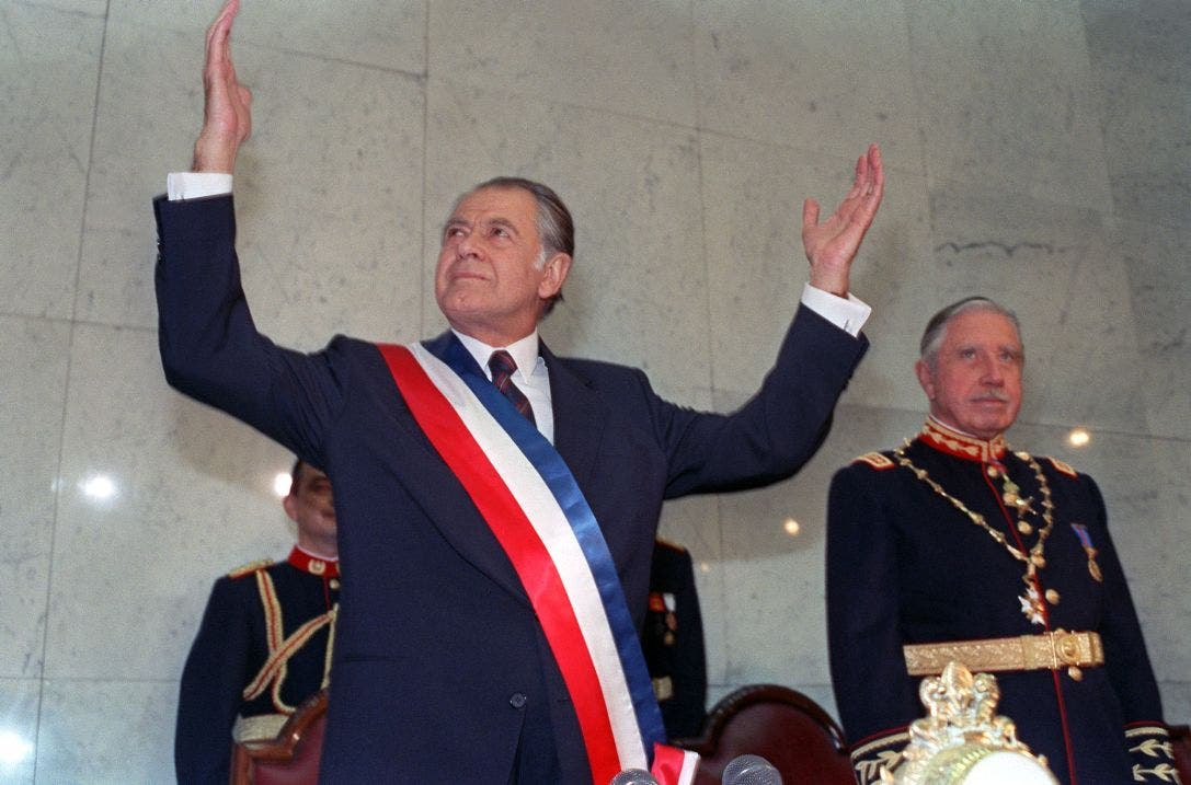 FILE - New Chilean President Patricio Aylwin (L) gestures on March 11, 1990 in Valparaiso, Chile, after receiving the presidential sash during inaugural ceremonies, as outgoing President Augusto Pinochet (R) looks on.  Patricio Aylwin, the first president of Chile after its return to democratic rule following Pinochet's dictatorship, died on April 19, 2016 at the age of 97. / AFP / STR