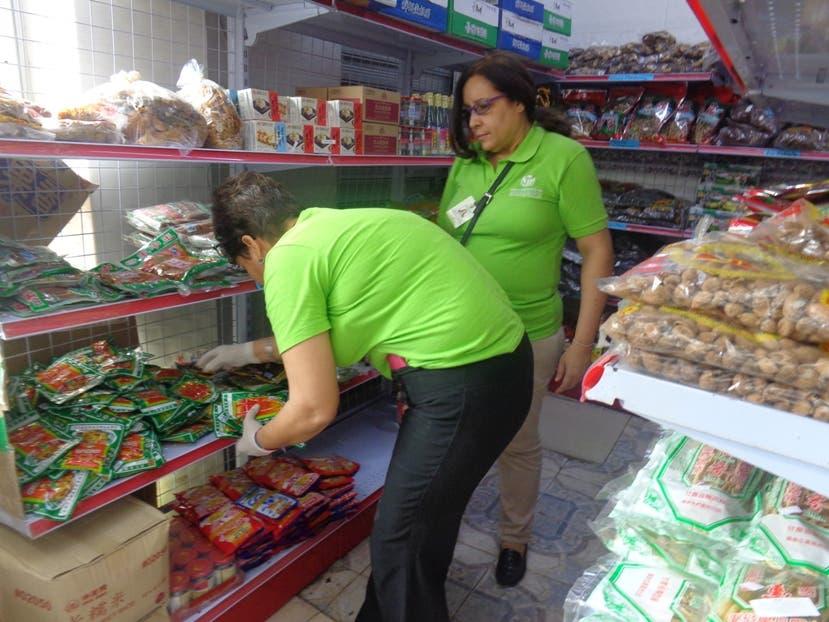 Dos empleadas de ProConsumidor en plena labor en uno de los establecimientos donde decomisaron productos. Foto de archivo.