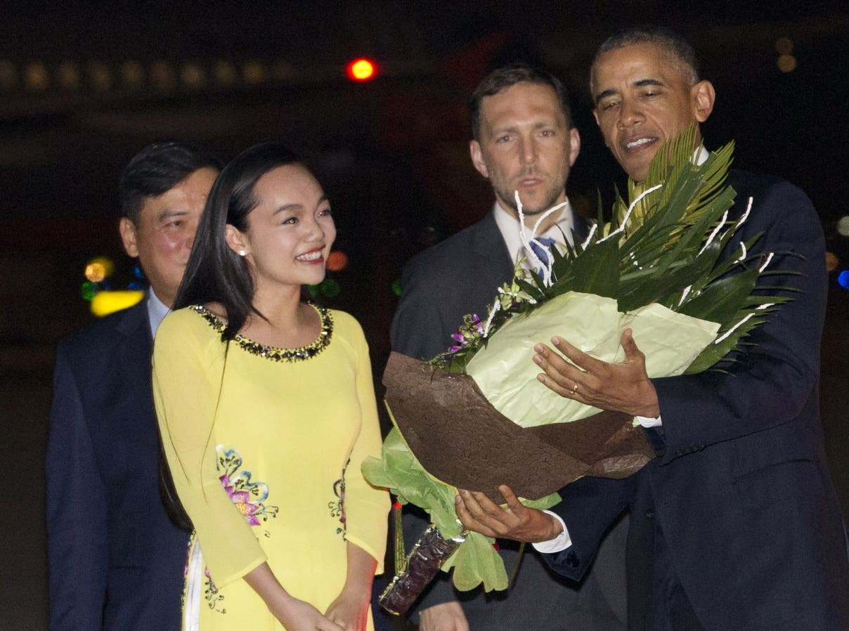 U.S. President Barack Obama is given flowers by Linh Tran, the ceremonial flower girl, as he arrives on Air Force One at Noi Bai International Airport in Hanoi, Vietnam, Sunday, May 22, 2016. The president is on a weeklong trip to Asia as part of his effort to pay more attention to the region and boost economic and security cooperation. (AP Photo/Carolyn Kaster)
