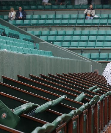 A few spectators wander around on center court of the French Open tennis tournament at the Roland Garros stadium in Paris, France, Monday, May 30, 2016. French Open organizers have announced the cancellation of all matches Monday at Roland Garros because of persistent rain forecast to last all day. (AP Photo/Michel Euler)