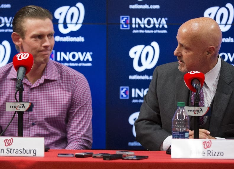 Washington Nationals pitcher Stephen Strasburg, left, looks on as Washington Nationals general manager Mike Rizzo speaks during a news conference to announce a seven-year contract extension that will pay Strasburg $175 million starting in 2017, at Nationals Park, on Tuesday, May 10, 2016, in Washington. (AP Photo/Evan Vucci)
