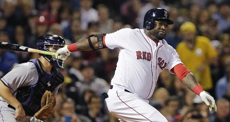 Boston Red Sox designated hitter David Ortiz follows through on a two-run double during the fourth inning of a baseball game against the Colorado Rockies in Boston, Tuesday, May 24, 2016. At left is Rockies catcher Dustin Garneau. (AP Photo/Charles Krupa)