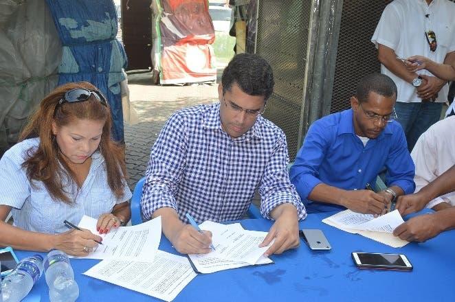 David Collado firma el acuerdo junto a Digna Reynoso y Maricio Collado