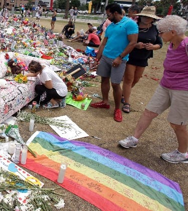 People visit a makeshift memorial honoring the victims of the Pulse nightclub mass shooting at the Dr. Phillips Performing Art Center, Monday, June 20, 2016, in Orlando, Fla. (AP Photo/John Raoux)