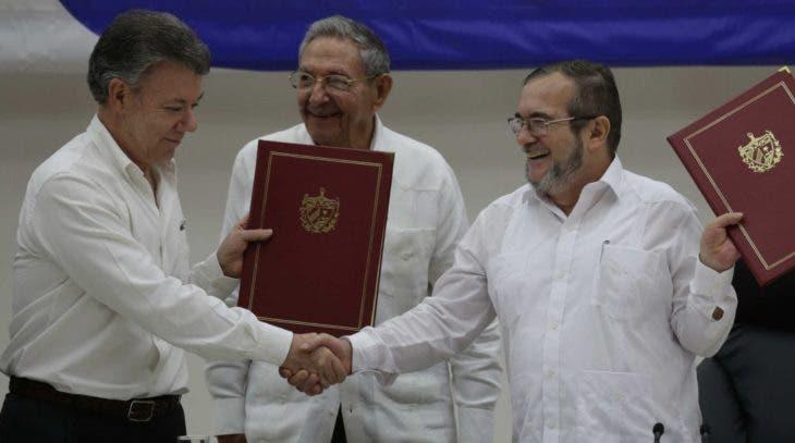 El presidente colombiano Juan Manuel Santos, izquierda, y el comandante de las FARC, Timoleón Jiménez, derechase estrechan las manos durante la ceremonia de firma de un acuerdo de cese al fuego y dejación de armas en La Habana, Cuba, jueves 23 de junio de 2016. En el centro, el presidente ciubano Raúl Castro. (AP Foto/Ramon Espinosa)
