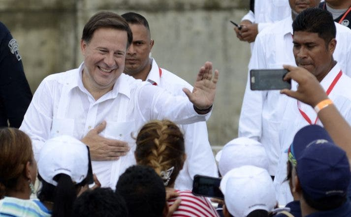 Panama's President Juan Carlos Varela waves after a Chinese merchant ship Cosco Shipping Panama crossed the new Agua Clara Locks of the Panama Canal during their inauguration in Colon, 80 km from Panama City on June 26, 2016 on June 26, 2016. A giant Chinese-chartered freighter nudged its way into the expanded Panama Canal on Sunday to mark the completion of nearly a decade of work forecast to boost global trade. / AFP / EDUARDO GRIMALDO