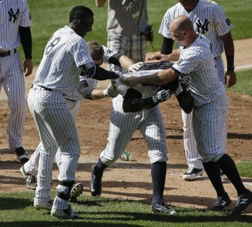 New York Yankees' Didi Gregorius (18), Chase Headley, second from left, and Brett Gardner, right, pull off Starlin Castro's jersey after Castro hit a walk-off home run against the Colorado Rockies during the ninth inning of a baseball game, Wednesday, June 22, 2016, in New York. The Yankees won 9-8. (AP Photo/Julie Jacobson)