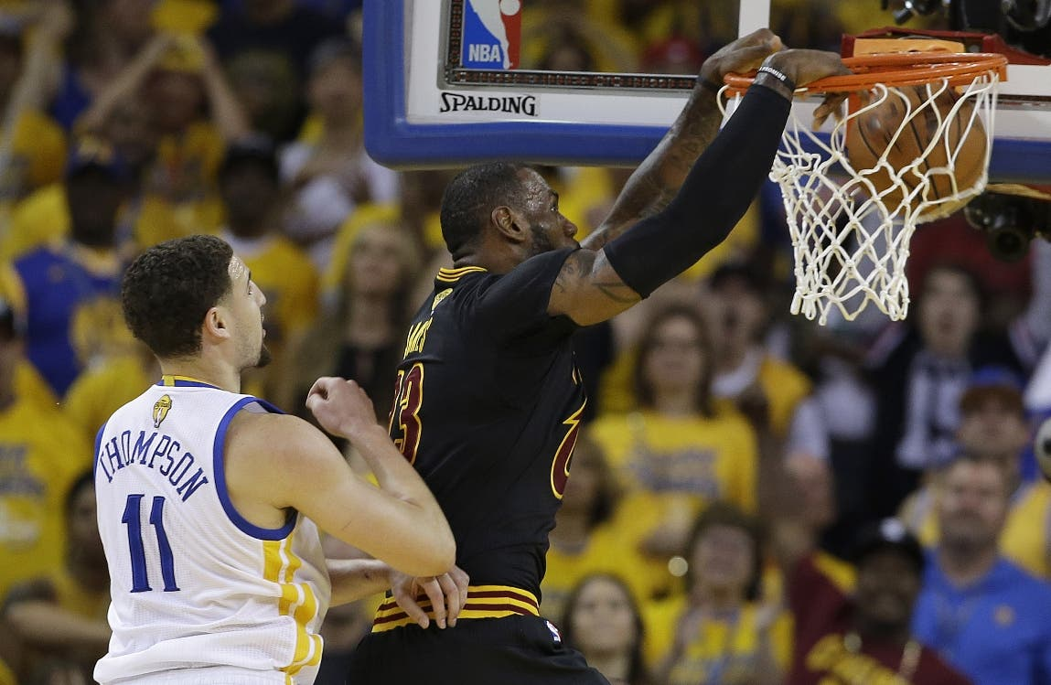 Cleveland Cavaliers forward LeBron James, right, dunks in front of Golden State Warriors guard Klay Thompson (11) during the first half of Game 7 of basketball's NBA Finals in Oakland, Calif., Sunday, June 19, 2016. (AP Photo/Marcio Jose Sanchez)