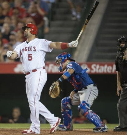 Los Angeles Angels' Albert Pujols watches his second three-run home run of the game in front of Texas Rangers catcher Robinson Chirinos in the fifth inning of a baseball game in Anaheim, Calif., Tuesday, July 19, 2016. (Kevin Sullivan/The Orange County Register via AP)
