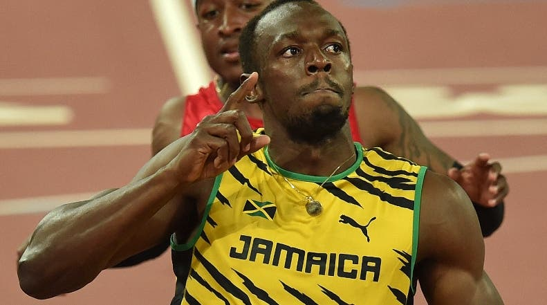 """Jamaica's Usain Bolt celebrates winning the final of the men's 100 metres athletics event at the 2015 IAAF World Championships at the """"Bird's Nest"""" National Stadium in Beijing on August 23, 2015.  AFP PHOTO / PEDRO UGARTE"""