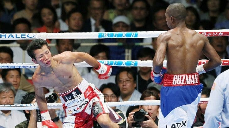 Shingo Wake (L) of Japan staggers after receiving a punch from Jonathan Guzman of the Dominican Republic during their IBF super-bantam weight title boxing bout in Osaka, western Japan on July 20, 2016. Japan OUT  / AFP / JIJI PRESS / STR