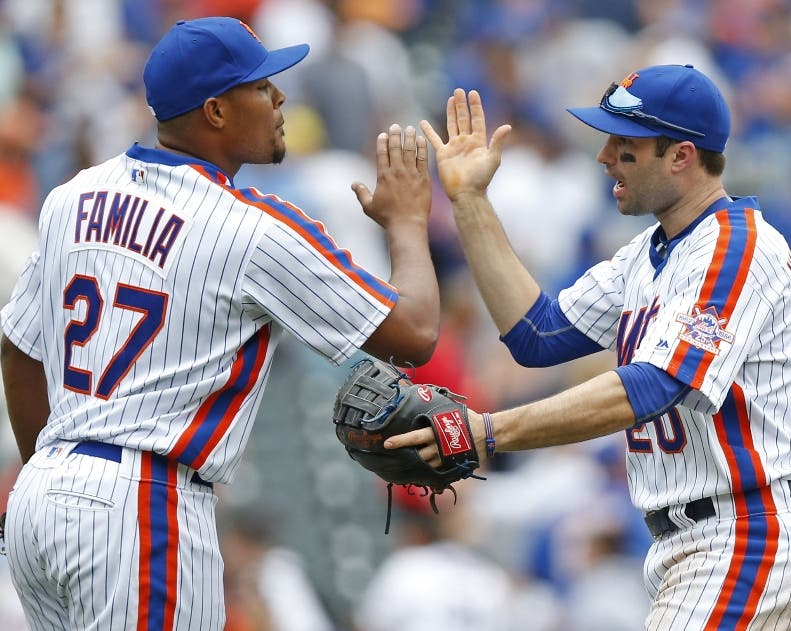 New York Mets relief pitcher Jeurys Familia (27) celebrates with second baseman Neil Walker (20) after closing out the Mets 6-4 victory over the Colorado Rockies in a baseball game, Sunday, July 31, 2016, in New York. (AP Photo/Kathy Willens)