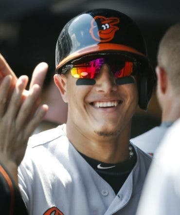 Teammates greet Baltimore Orioles Manny Machado in the dugout after he scored on J.J. Hardy's first-inning, two-run single during a baseball game against the New York Yankees in New York, Thursday, July 21, 2016. (AP Photo/Kathy Willens)
