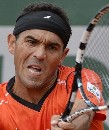 Dominican Republic's Victor Estrella Burgos hits a return to Poland's Jerzy Janowicz during their French tennis Open first round match at the Roland Garros stadium in Paris on May 25, 2014. AFP PHOTO / MIGUEL MEDINA
