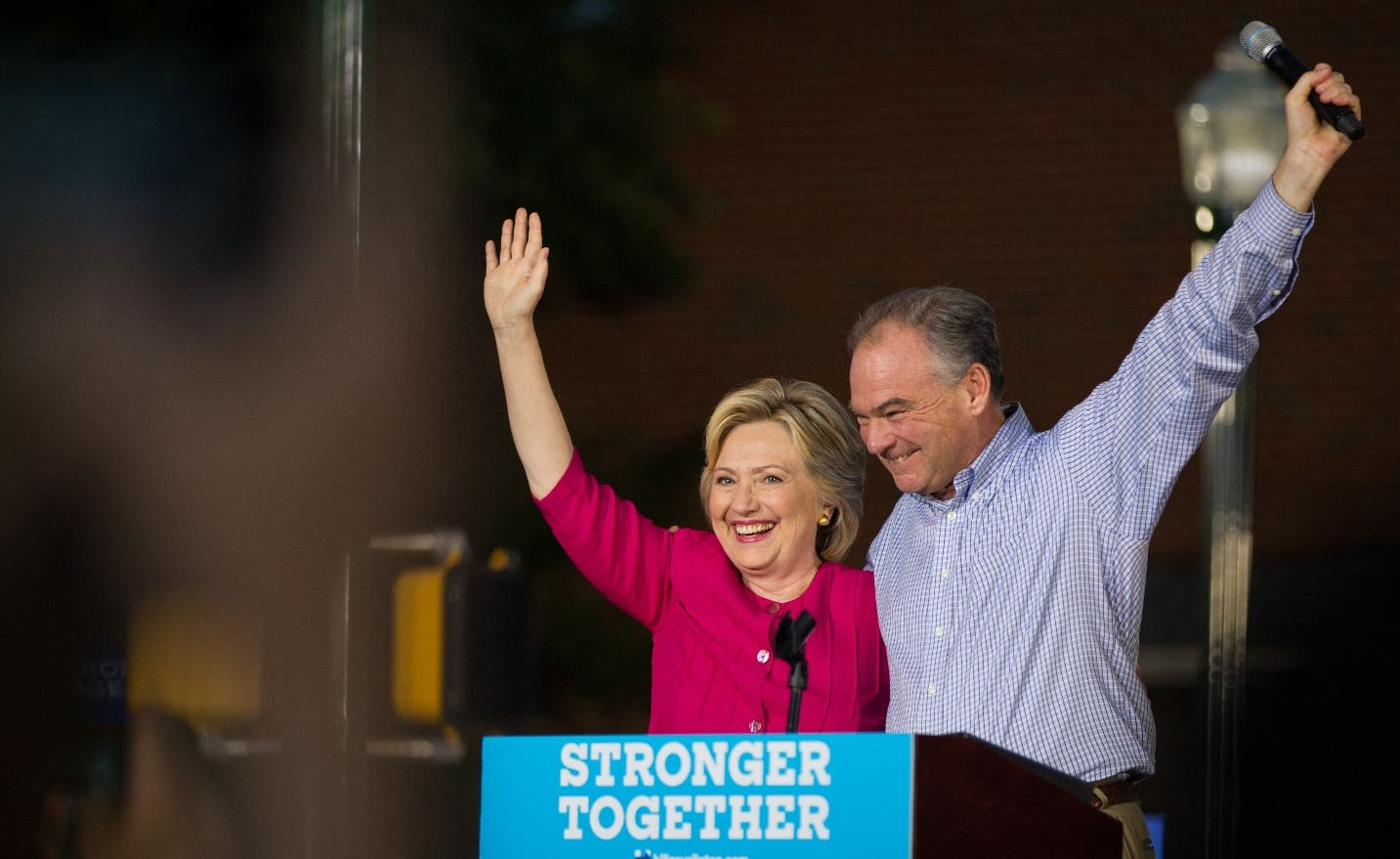 Democratic presidential candidate Hillary Clinton and vice presidential candidate Tim Kaine wave during a rally at Broad Street Market in Harrisburg, Pa., Friday, July 29, 2016. Clinton and Kaine begin a three day bus tour through the rust belt. (Alex Driehaus/PennLive.com via AP)