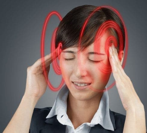 Young woman is touching her head, the temporal region of red color