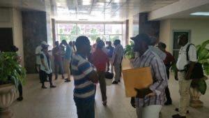 Miembros se encuentran en los pasillos con documentos en las manos.