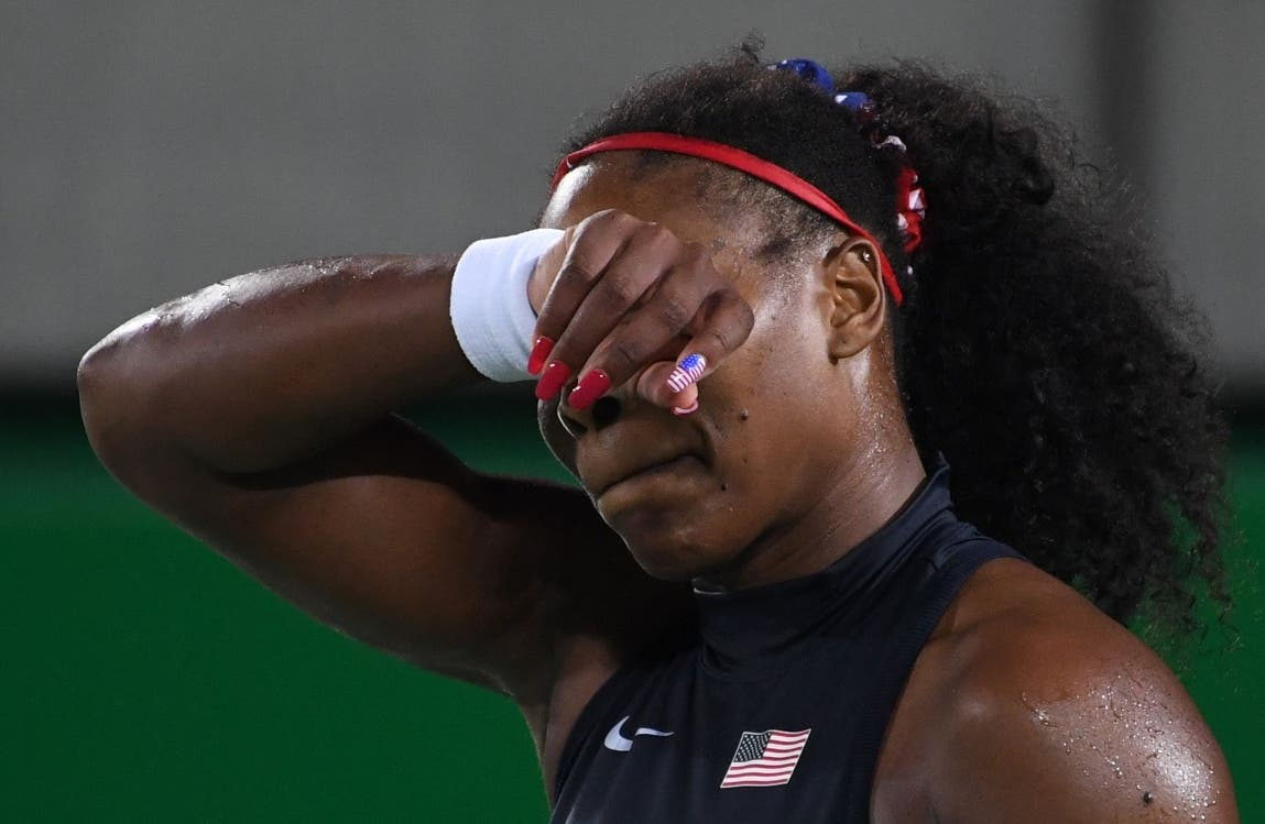 TOPSHOT - USA's Serena Williams reacts after losing a point during her women's third round singles tennis match agaisnt Ukraine's Elina Svitolina at the Olympic Tennis Centre of the Rio 2016 Olympic Games in Rio de Janeiro on August 9, 2016. / AFP / Luis Acosta