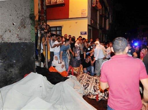 Una multitud observa cuerpos cubiertos con sábanas después de que se registrara una explosión en una boda en Gaziantep, en el sureste de Turquía, el domingo 21 de agosto de 2016. El gobernador de la provincia de Gaziantep, Ali Yerlikaya, dijo que el estallido cerca de la frontera con Siria fue un acto terrorista. (Eyyup Burun/DHA vía AP)
