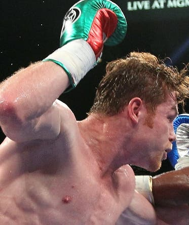 Boxers Canelo Alvarez of Mexico (L) trades punches with Floyd Mayweather Jr. of US (R) during their WBC/WBA 154-pound title fight the MGM Grand Garden Arena, September 14, 2013 in Las Vegas, Nevada. Mayweather won a majority decision.  AFP PHOTO / John GURZINSKI