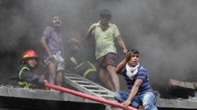 A volunteer communicates with others on the ground as he helps douse a fire at a packaging factory in Tongi industrial area outside Dhaka, Bangladesh, Saturday, Sept. 10, 2016. A boiler exploded and triggered a fire at a packaging factory near Bangladesh's capital. (AP Photo/A. M. Ahad)