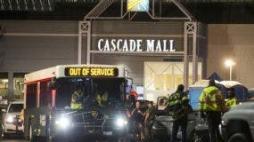 Emergency personnel stand in front of an entrance to the Cascade Mall at the scene of a shooting where several people were killed Friday, Sept. 23, 2016, in Burlington, Wash. Police searched Saturday for a gunman who opened fire in the makeup department of a Macy's store at the mall north of Seattle, killing several females, before fleeing toward an interstate on foot, authorities said. (AP Photo/Stephen Brashear)